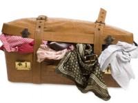 Вещи собранные в чемодан. Тщательная упаковка личных вещей для переезда.